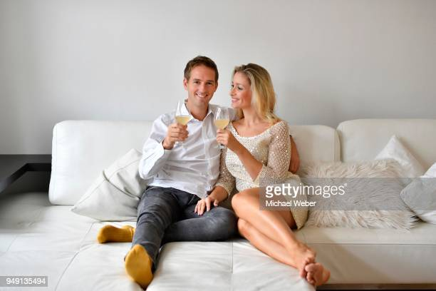 Man, woman, couple on sofa, in love, wine, glass, looking at camera