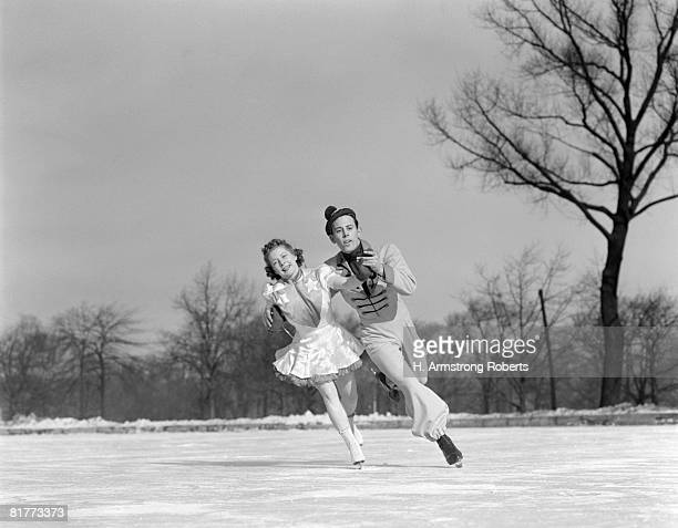 man woman couple pair figure skating on ice rink smiling costumes arm in arm leaning precision glide dance. - figure skating stock pictures, royalty-free photos & images