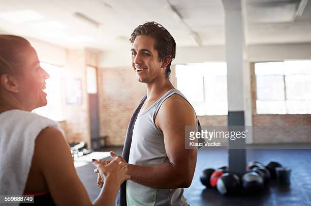 Man & woman laughing after gym session