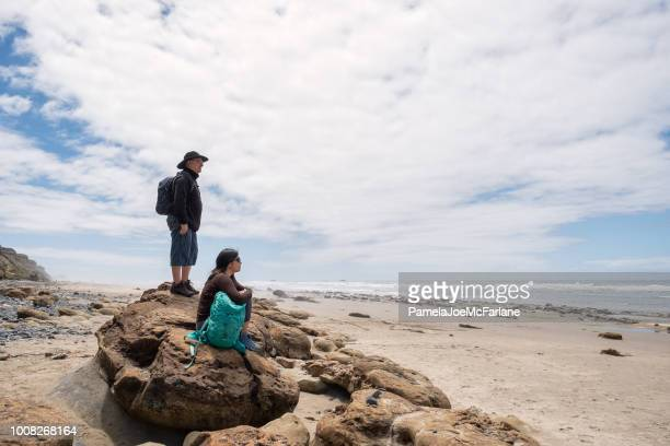 man, woman looking at ocean from rocks on beach, oregon - oregon coast stock pictures, royalty-free photos & images