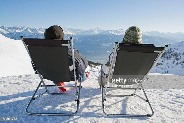 man, woman relax on deck chairs in snow - cadeira dobrável - fotografias e filmes do acervo