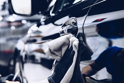 Man worker in car wash polishing car with cloth 1152422096