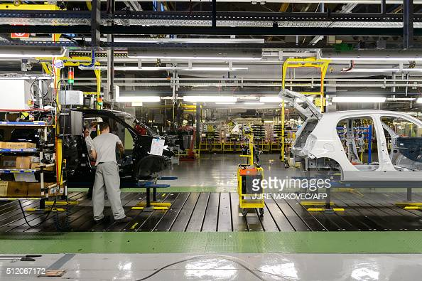 a man worker instals interior parts on a car production line at the manufacturing subsidiary. Black Bedroom Furniture Sets. Home Design Ideas