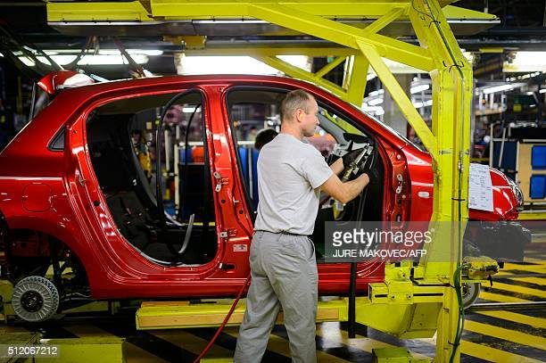A man worker instals interior parts on a car production line at the manufacturing subsidiary factory of Renault in Slovenia Revoz in Novo mesto on...