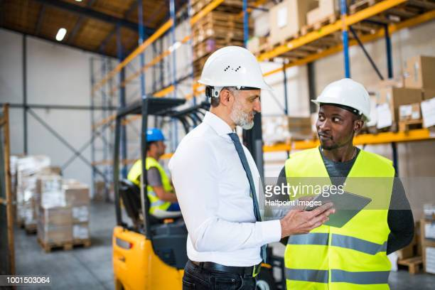 Man workers and manager with tablet working in a warehouse.