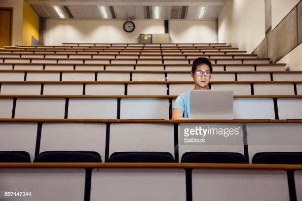 mann arbeitet alleine in einem seminarraum - hörsaal stock-fotos und bilder