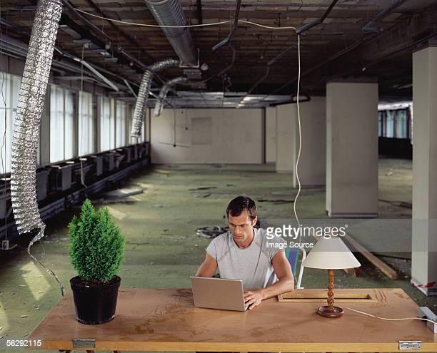 Un homme travaillant seul dans un bureau désordonné