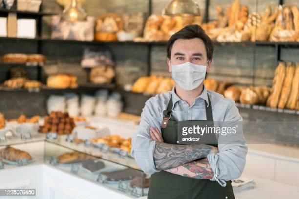 コロナウイルスを避けるためにフェイスマスクを着用したパン屋で働く男性 - パン屋 ストックフォトと画像