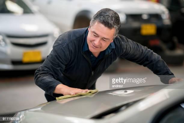 Man working at a car garage polishing the vehicles
