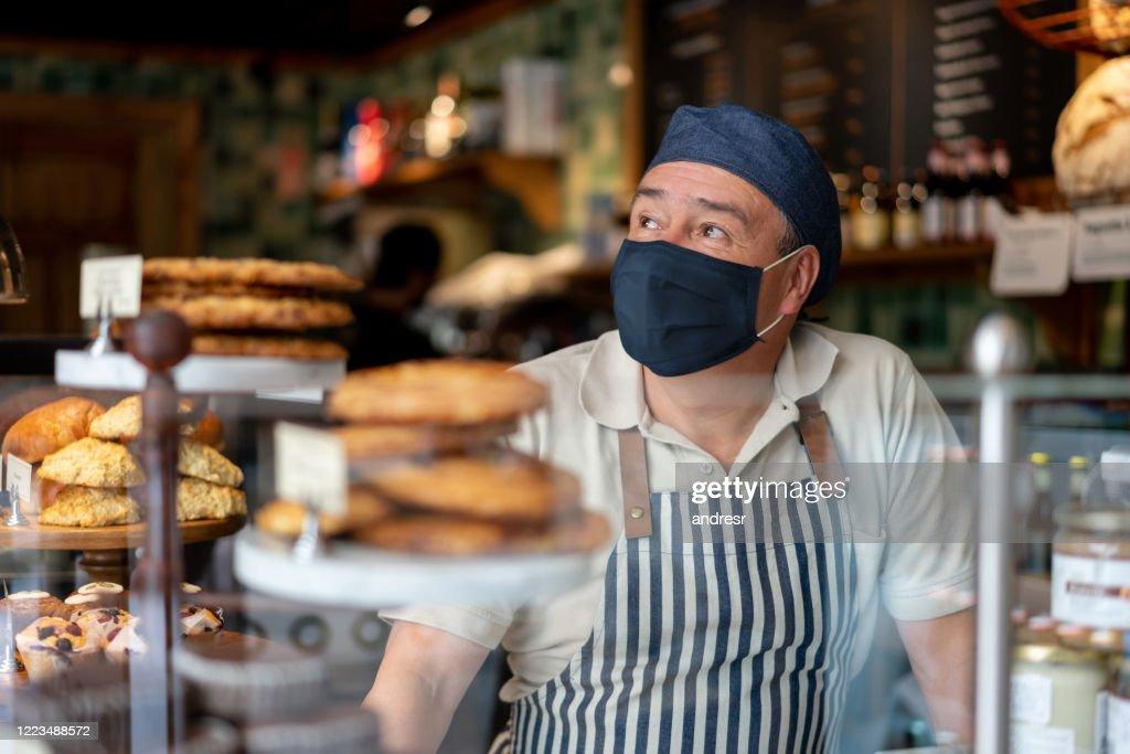 Mens die bij een koffiewinkel werkt die een facemask draagt : Stockfoto