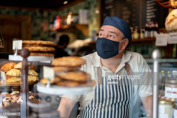 man working at a coffee shop wearing a facemask - protective face mask stock pictures, royalty-free photos & images