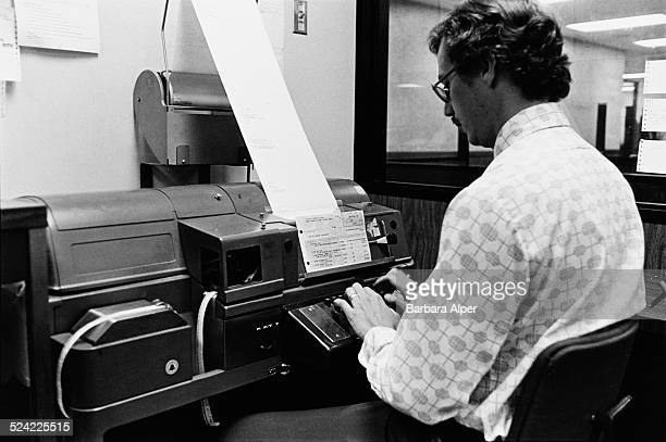 A man working at a computer in the back office of the Dean Witter Reynolds stock brokerage firm Boston Massachusetts USA August 1976