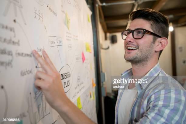 Mann arbeitet in einem kreativen Büro zeigt auf einen Business-plan