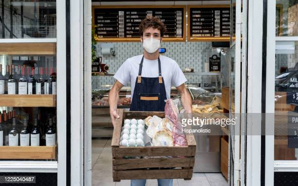 man working at a deli preping delivery orders for customers and wearing a facemask - opening event stock pictures, royalty-free photos & images
