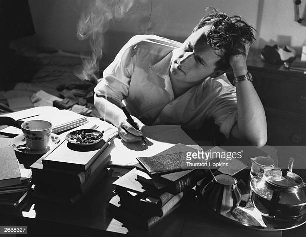 Man working at a desk while studying a correspondence course. Original Publication: Picture Post - 8639 - Learning Through The Letter Box - pub. 1956