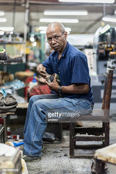 man working at a factory making shoes - leather shoe stock pictures, royalty-free photos & images