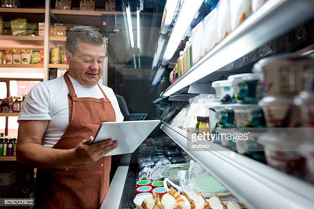man working at a grocery store - business owner stock photos and pictures