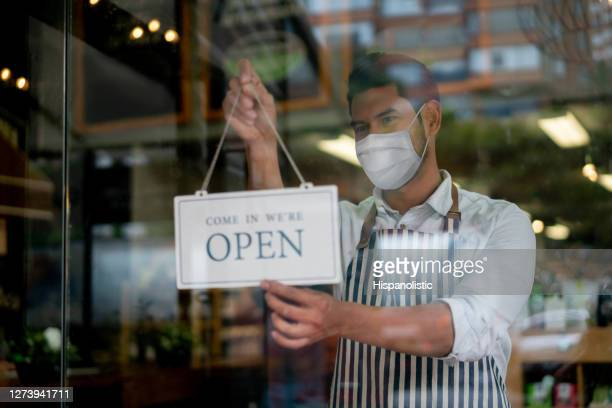 man working at a grocery store wearing a facemask and hanging an open sign on the door - opening event stock pictures, royalty-free photos & images