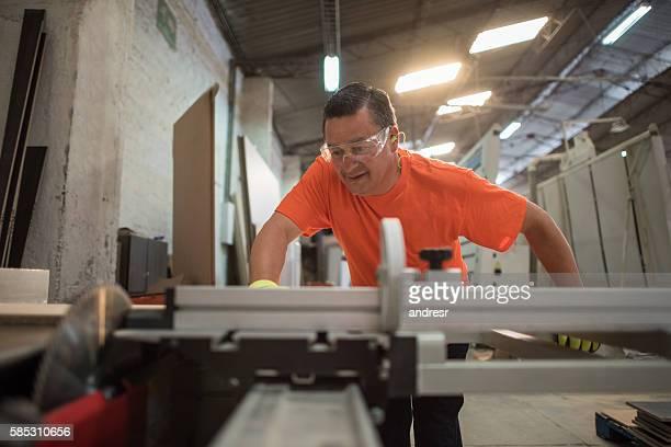 Man working at a lumberyard cutting wood