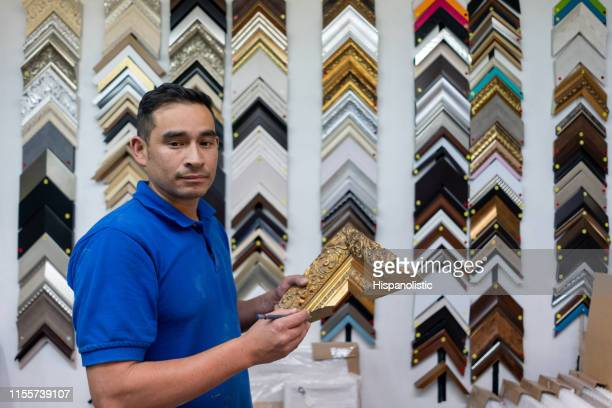 man working at a marquetry holding frame samples - hispanolistic stock photos and pictures