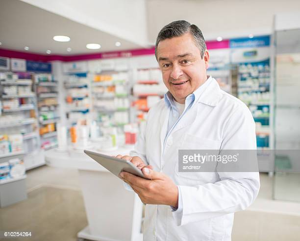 Man working at a pharmacy using a tablet computer