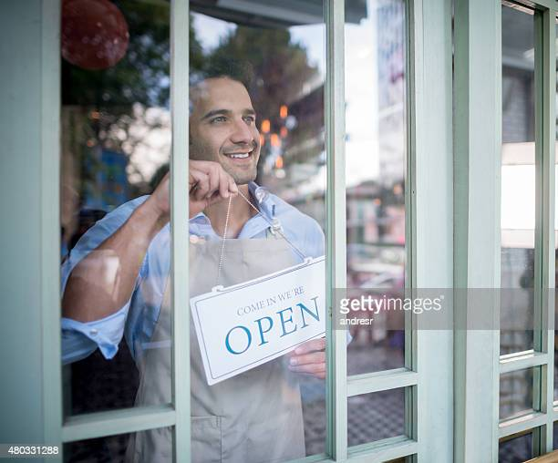 Man working at a restaurant hanging an open sign