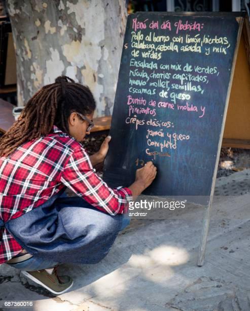 黒板にメニューを書くレストランで働いていた男性