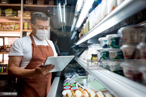 man working at a supermarket wearing a facemask while doing the stock inventory - biosecurity stock pictures, royalty-free photos & images