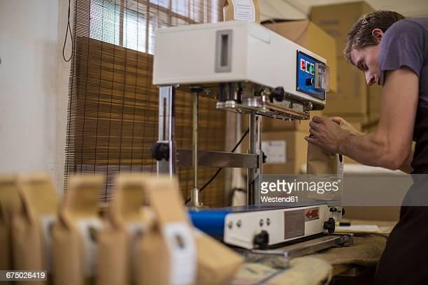man working at coffee bean packaging vacuum sealer - maschinenteil hergestellter gegenstand stock-fotos und bilder