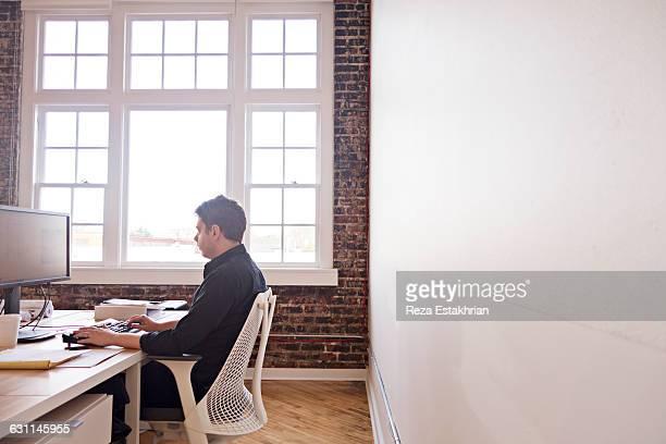 man working at computer in modern office - un solo hombre fotografías e imágenes de stock
