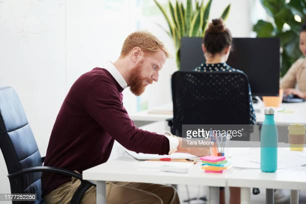 man working at desk in office - pen stock pictures, royalty-free photos & images
