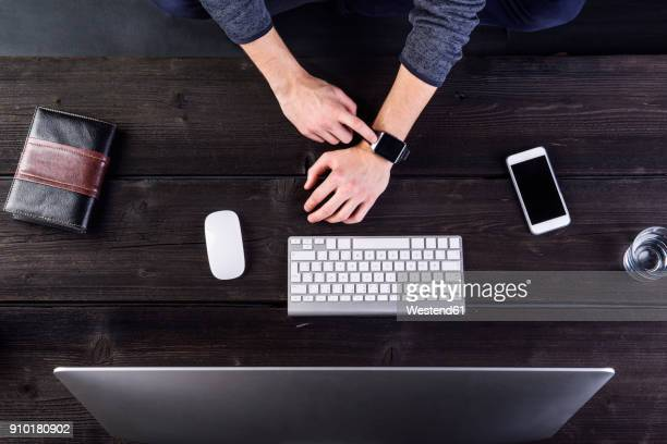 Man working at desk with computer, sychronizing smart watch