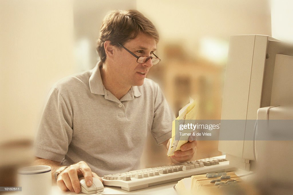 Man working at home computer, smiling : Stockfoto