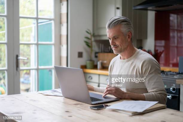 man working at home on his laptop computer - the internet stock pictures, royalty-free photos & images