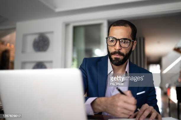 ラップトップを使用して、自宅で働く男 - 金融関係の職業 ストックフォトと画像