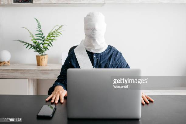 man working at home with his head covered in toilet paper - funny toilet paper stock pictures, royalty-free photos & images