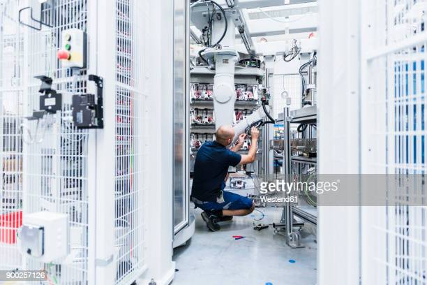 Man working at industrial robot in modern factory