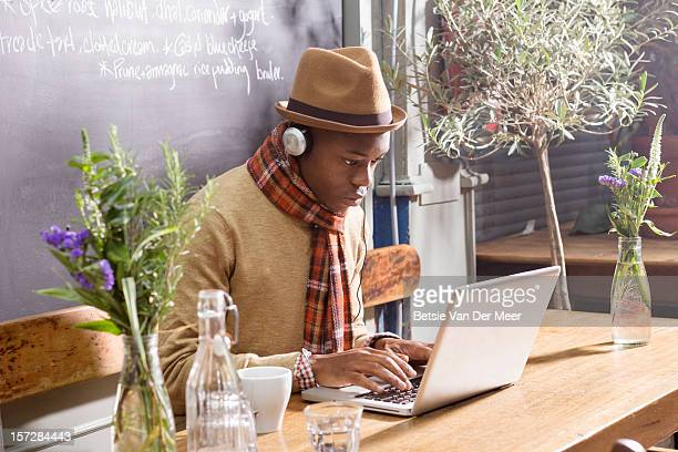 Man working at laptop in pavement cafe.