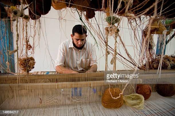 Man working at loom in carpet workshop.