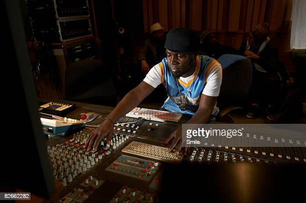 man working at mixing desk group chatting in back - recording studio stock pictures, royalty-free photos & images