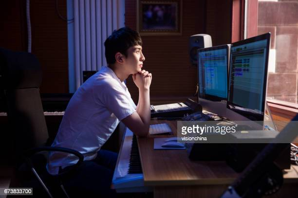 man working at mixing panel in a recording studio - chinese music stock pictures, royalty-free photos & images