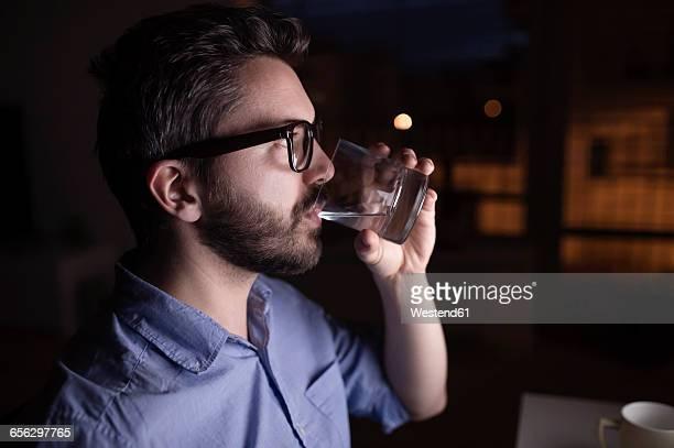 Man working at night, drinking water