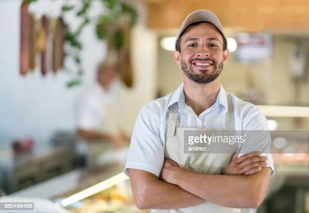 man working at the butcher's shop - happy merchant stock pictures, royalty-free photos & images