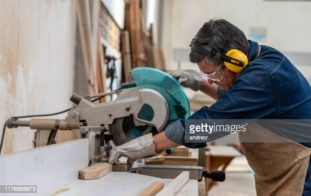 man working at the carpentry cutting wood with a saw machine - ear protection stock pictures, royalty-free photos & images