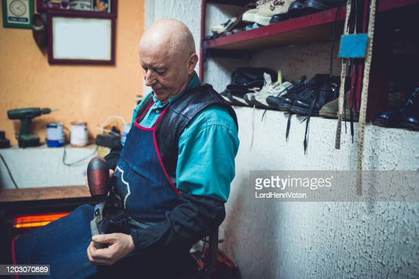 靴屋で働く男性 - フラットフィッシュ ストックフォトと画像