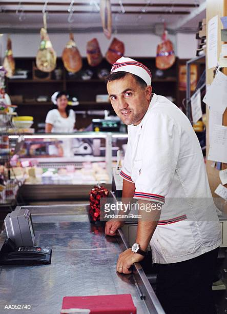 Man working behind counter in delicatessen, Italy (selective focus)