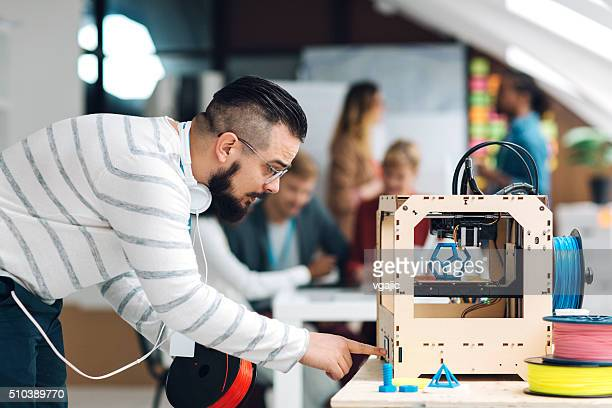 man working by 3d printer in start-up business office. - 3d printing stock pictures, royalty-free photos & images