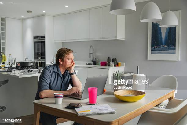 man working from his dining table - homework stock pictures, royalty-free photos & images