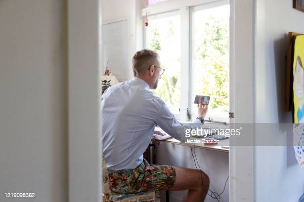 man working from home in a makeshift office in a child's bedroom - working from home stock pictures, royalty-free photos & images