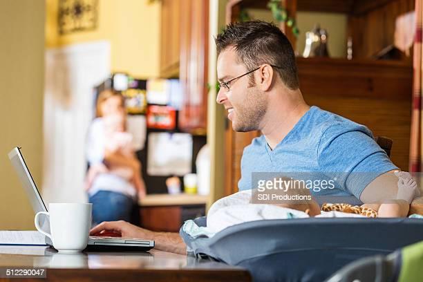 Homme travaillant de la maison bureau tout en prenant soin de bébé